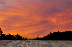 Wooden deck overlooking a red sunset Royalty Free Stock Photo