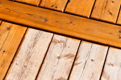 Wooden deck pattern partially stained transparent. Wooden deck boards partially finished with transparent protective outdoor decking paint stain and partially royalty free stock images