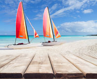 Wooden deck perspective with two colorful catamarans Stock Images