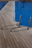 Wooden deck and pool. A view of a wooden deck beside an outdoor swimming pool stock photo