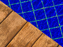 Wooden deck pool. Details of wooden planking on a poolside deck with the blue mosaic pool bottom in the background stock image