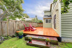 Wooden deck with red chairs. Fenced backyard view. View of deck with red chairs after rain Stock Photography