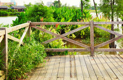 Wooden deck wood patio outdoor garden terrace. Corner of empty wood deck, wooden patio, terrace with balustrade by riverside in garden Royalty Free Stock Image