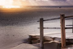 Wooden deck in the sand by the beach at sunset. Wooden deck in the sand by the ocean at sunset stock photos