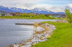 Wooden deck on a scenic lake with rocks and bright green grasses on the shore. Bridge and houses can be seen against snowy mountain and cloudy sky in the stock photos