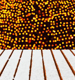 Wooden deck with snow and Christmas lights background. Royalty Free Stock Images