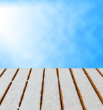 Wooden deck with snow and sky background. Royalty Free Stock Photos