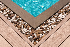 Wooden deck and stone at the corner of swimming pool. Wooden deck and stone at the corner of a swimming pool royalty free stock images