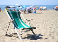 Wooden deck on sunny beach with umbrellas in summer 2 Stock Image