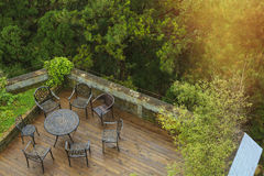 Wooden deck surrounded by trees with seating arrangement Royalty Free Stock Image