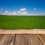 Wooden deck table over beautiful meadow with blue sky Stock Photos