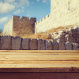 Wooden deck table over old city wall Royalty Free Stock Photography