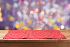 Wooden deck table with polka dots tablecloth over bokeh lights background stock photo