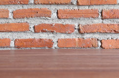 Wooden deck table with red brick wall. Pattern Royalty Free Stock Image