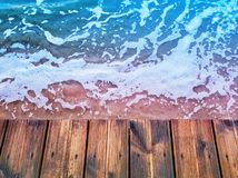 Wooden deck waterfront floor background texture and blue sea water surface with foam royalty free stock photo