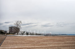 Wooden deck in the waterfront of Thessaloniki, Greece, under a cloudy sky Stock Images