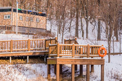 Wooden deck in a wooded area covered in snow Stock Image