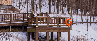 Wooden deck in a wooded area covered in snow Stock Photography