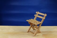 A wooden deckchair on a beach. A wooden deck chair as a symbol of vacation and relaxation on a blue background Stock Images