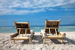 Wooden deckchairs on empty beach Stock Image