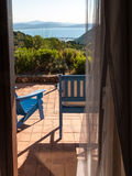 Wooden deckchairs on the patio in front of the sea. Two blue wooden deckchairs on the patio of a villa on the sea views from inside Stock Images