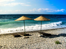 Wooden deckchairs under umbrellas on beach. Royalty Free Stock Photos