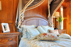 Wooden decorated bedroom and furniture. Elaborate style bedroom internal, with featured wooden wall and flowery curtain decoration, shown as luxury, classical Royalty Free Stock Photography