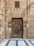 Wooden decorated copper plated door and stone bricks wall at the courtyard of Al-Sultan Barquq mosque, Old Cairo, Egypt. Wooden decorated copper plated door and stock photos