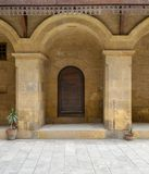 Wooden decorated door framed by arched bricks stone wall. At caravansary Wikala of Bazaraa, suited in Tombakshia street, Al Gamalia district, Medieval Cairo Royalty Free Stock Images