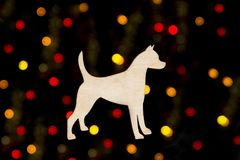 Wooden decoration in the form of a dog silhouette on a background of yellow and red bokeh lights on a black background Royalty Free Stock Image