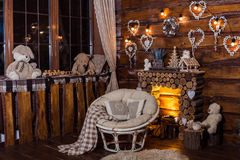 Wooden decorative fireplace, papasan chair and romantic bulbs Royalty Free Stock Images
