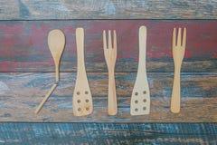 Wooden, decorative kitchen utensils with a broken spoon Stock Photos