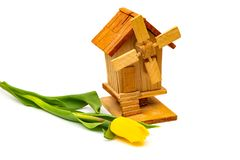Wooden decorative mill with tulips on a white background. Village farm buildings stock photos