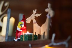 Wooden deer with a candle light and Santa Clause. stock photography