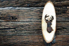 Wooden deer on wooden plank Royalty Free Stock Photography
