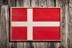 Wooden Denmark flag. 3d rendering of Denmark flag on a wooden frame over a planks wall Stock Photos