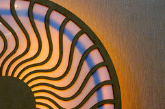 Wooden design with circles connected by wavy lines. Wooden design of two circles connected by wavy lines and lit by colorful lights. Can denote the circle of Stock Photo