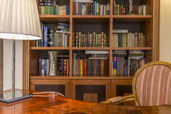Wooden desk and classic bookcase with books royalty free stock photo