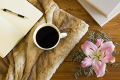 Wooden desk with a cup of coffee, notebook and flower. Soft fur on the table creates a girly, romantic and cozy atmosphere Royalty Free Stock Photography
