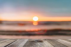 Wooden desk of free space with sea background at sunset.  stock photos