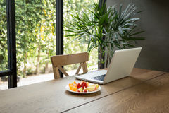 Wooden desk with fresh fruits and laptop with green plant. In background Royalty Free Stock Photos