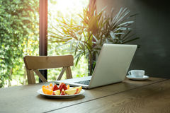 Wooden desk with fresh fruits and laptop with green plant. In background Royalty Free Stock Image