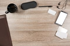Wooden desk with smartphone, headphones, name tag, pen, coffee m. Top view on wooden desk with smartphone with empty copy space, black headphone earpieces and Royalty Free Stock Image