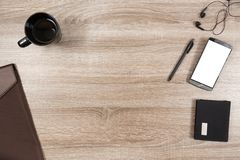 Wooden desk with smartphone, headphones, pen, wallet, coffee mug. Top view on wooden desk with smartphone with empty copy space, black headphone earpieces and Stock Images