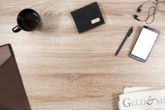 Wooden desk with smartphone, headphones, pen, wallet, coffee mug stock photo