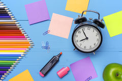 Wooden desk with stationery and empty stickers, Alarm clock and apple. Conceptual background in the style of Back to School Royalty Free Stock Image