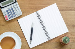 Wooden desk table with notebook, pen, calculator and cup of coff. Ee. Top view with copy space, flat lay Royalty Free Stock Image