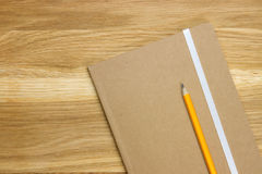 Wooden desk top with notebook and pencil. Top-view of wooden desk top with notebook and orange pencil Stock Images