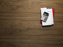 Wooden desktop. Brown wooden desktop with calculator and invoices Stock Photos