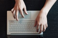Wooden desktop top view, male hands typing on the laptop keyboard royalty free stock photo